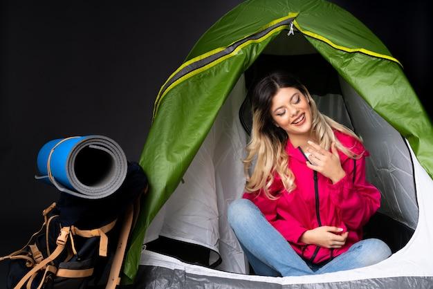 Ragazza dell'adolescente dentro una tenda verde di campeggio isolata sulla parete nera che sorride molto