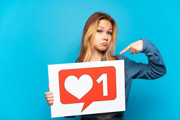 Ragazza adolescente su sfondo blu isolato che tiene un cartello con l'icona mi piace e lo punta