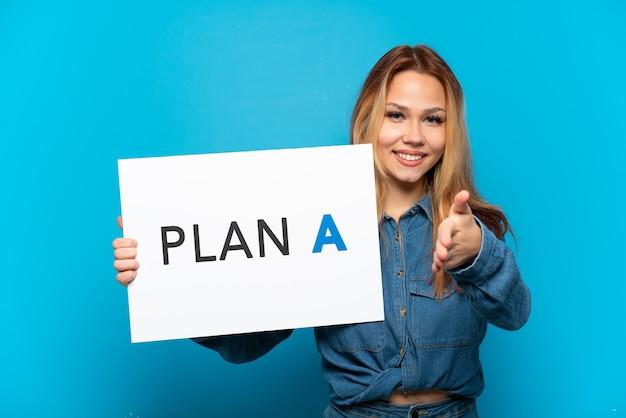 Ragazza adolescente su sfondo blu isolato con in mano un cartello con il messaggio piano a che fa un accordo