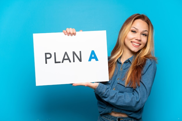 Ragazza adolescente su sfondo blu isolato con in mano un cartello con il messaggio piano a con espressione felice