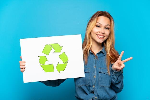 Ragazza adolescente su sfondo blu isolato che tiene un cartello con l'icona di riciclo e celebra una vittoria