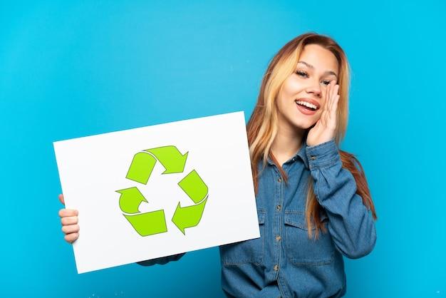 Ragazza adolescente su sfondo blu isolato che tiene un cartello con l'icona di riciclo e grida