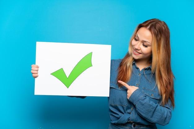 Ragazza adolescente su sfondo blu isolato che tiene un cartello con l'icona del segno di spunta verde del testo e lo punta