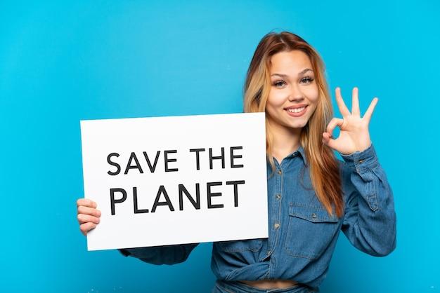 Ragazza adolescente su sfondo blu isolato che tiene un cartello con il testo salva il pianeta e celebra una vittoria