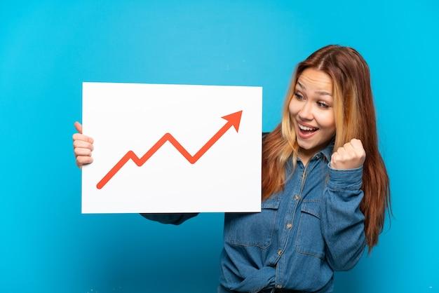 Ragazza adolescente su sfondo blu isolato con in mano un cartello con un simbolo di freccia statistica in crescita e celebrando una vittoria