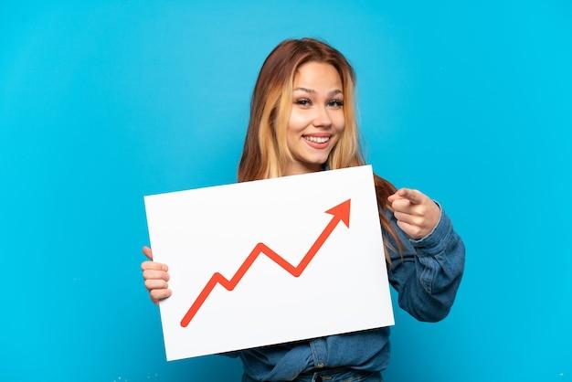 Ragazza adolescente su sfondo blu isolato con in mano un cartello con un simbolo di freccia statistica in crescita e rivolto verso la parte anteriore