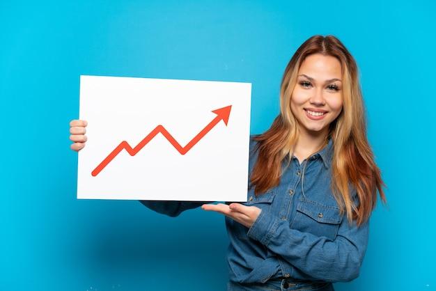 Ragazza adolescente su sfondo blu isolato con un cartello con un simbolo di freccia di statistiche in crescita
