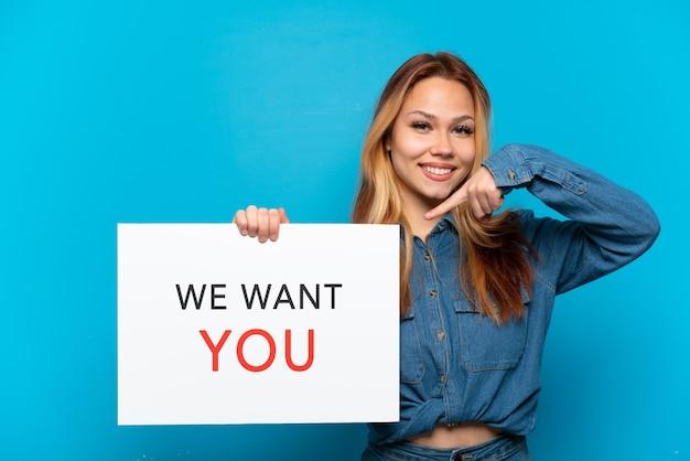 Ragazza adolescente su sfondo blu isolato tenendo we want you board e indicandolo