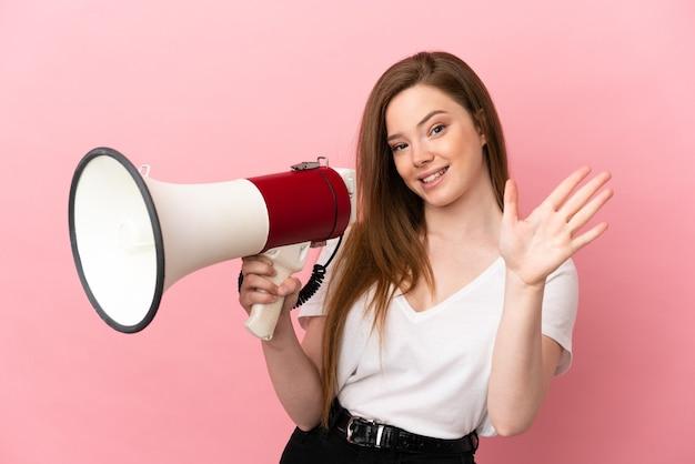 Ragazza dell'adolescente sopra fondo rosa isolato che tiene un megafono e che saluta con la mano con l'espressione felice