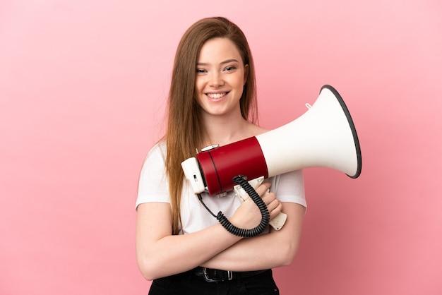 Ragazza adolescente su sfondo rosa isolato con in mano un megafono e sorridente