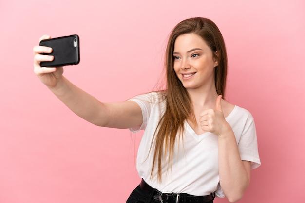 Ragazza adolescente su sfondo rosa isolato facendo un selfie con il telefono cellulare mobile