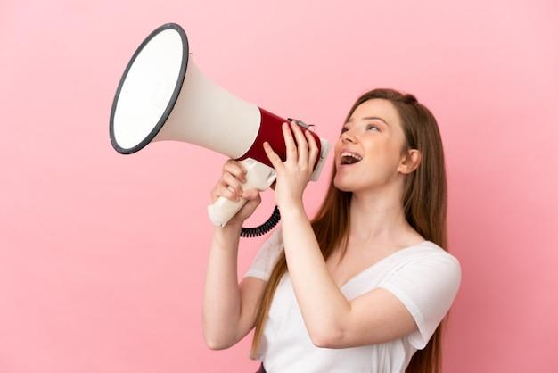 Ragazza adolescente su sfondo rosa isolato che grida attraverso un megafono per annunciare qualcosa in posizione laterale