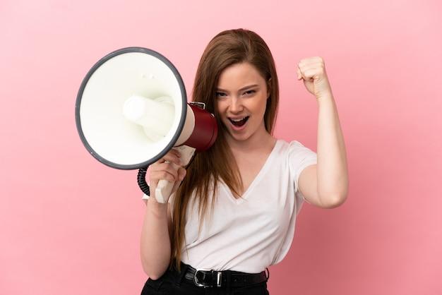Ragazza adolescente su sfondo rosa isolato che grida attraverso un megafono per annunciare qualcosa