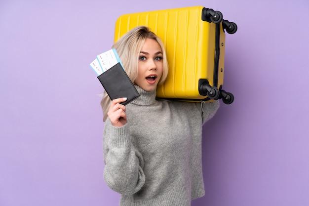 Ragazza dell'adolescente sopra la parete viola isolata in vacanza con la valigia e passaporto e sorpresa