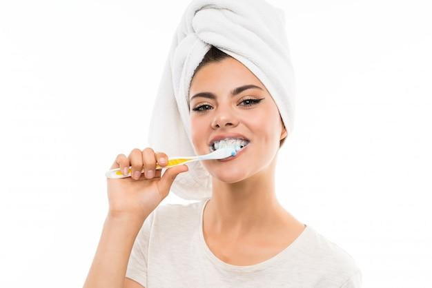 Ragazza dell'adolescente sopra la parete bianca isolata che pulisce i suoi denti