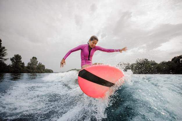 La ragazza dell'adolescente che salta sul wakeboard arancione