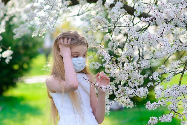 Ragazza dell'adolescente nella mascherina medica nel giardino fiorito di primavera. concetto di distanza sociale e prevenzione del coronavirus.