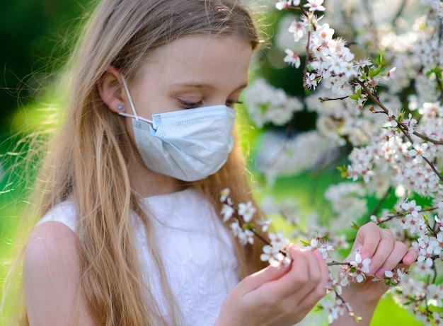 Ragazza dell'adolescente nella mascherina medica nel giardino di fioritura di primavera