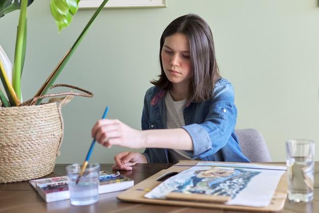 Ragazza adolescente che dipinge con acquerelli, seduta a casa al tavolo. arte, educazione, creatività, hobby adolescenziali
