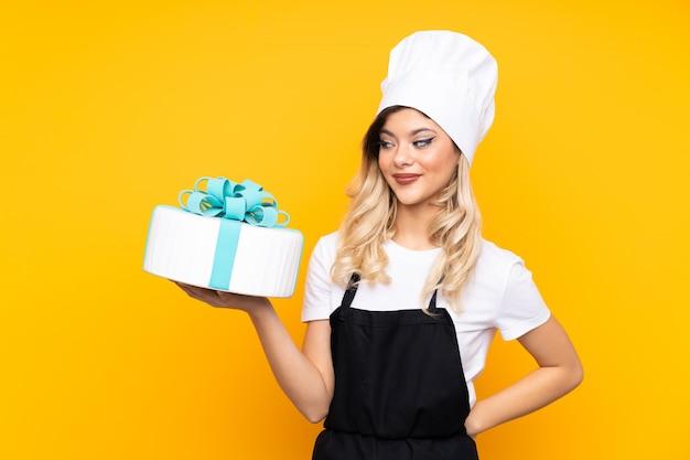 Pasticceria della ragazza dell'adolescente che tiene una grande torta