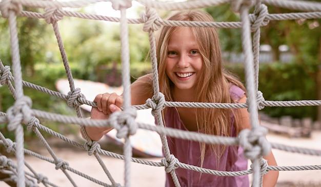 Ragazza adolescente nel parco giochi sulla scala di corda