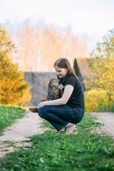 La ragazza adolescente che gioca con il suo adorabile gatto grigio a strisce all'aperto sullo sfondo della natura primaverile in campagna.