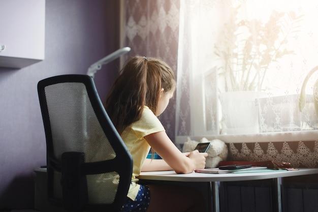 La ragazza dell'adolescente si siede a un tavolo di fronte a una finestra e scrive qualcosa su un taccuino.