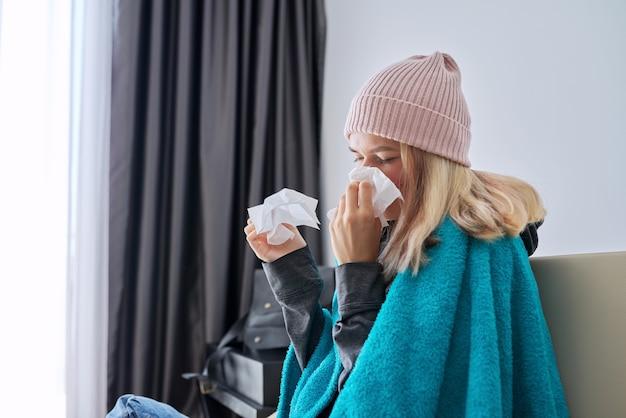 Ragazza adolescente che starnutisce nel fazzoletto, femmina con sintomi di malattia seduta a casa coperta da una coperta calda e indossa un cappello lavorato a maglia