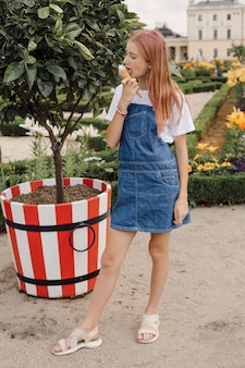 Ragazza adolescente in piedi vicino all'albero in abito di jeans che mangia gelato in una calda giornata estiva, foto