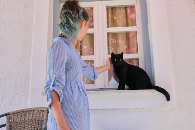 Ragazza dell'adolescente che tocca bello gatto nero che si siede sul davanzale della finestra all'aperto, soleggiata giornata estiva