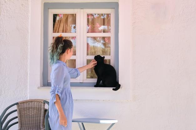Ragazza dell'adolescente che tocca bello gatto nero che si siede sul davanzale della finestra all'aperto