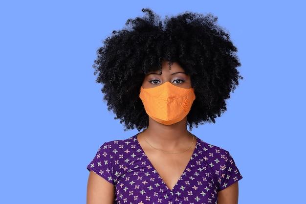 Ragazza adolescente che indossa una maschera di protezione facciale contro covid-19 isolata su sfondo blu