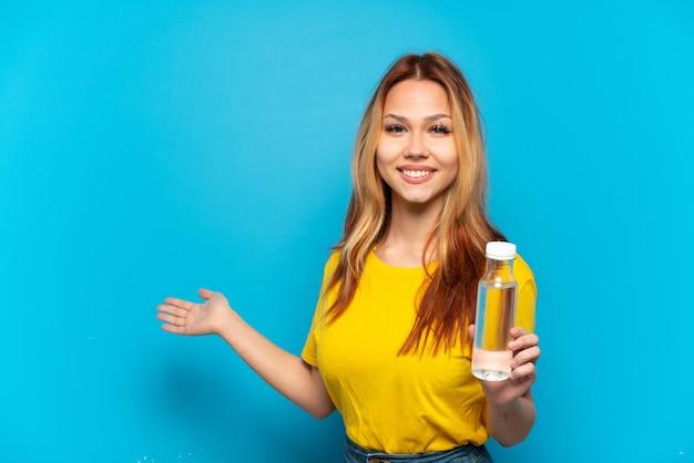 Ragazza adolescente con una bottiglia d'acqua su sfondo blu isolato che allunga le mani di lato per invitare a venire