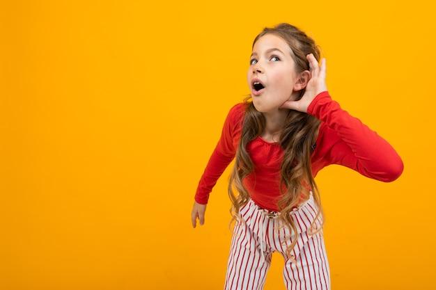 Ragazza adolescente con capelli ricci in una camicetta rossa e pantaloni a righe ascolta i suoni su uno sfondo arancione con spazio di copia.