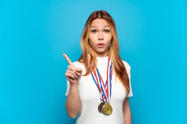 Ragazza adolescente con medaglie su sfondo isolato che intende realizzare la soluzione mentre si alza un dito