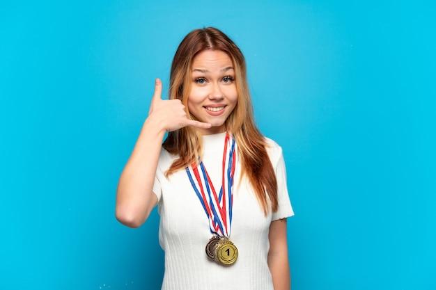 Ragazza adolescente con medaglie su sfondo isolato che fa il gesto del telefono. richiamami segno