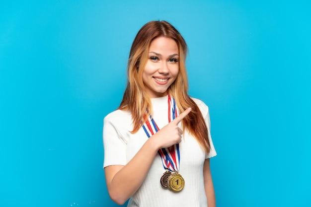Ragazza adolescente con medaglie su sfondo isolato che punta di lato per presentare un prodotto