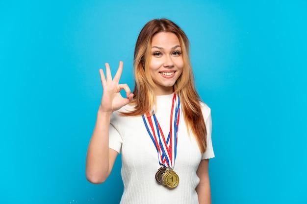 Ragazza adolescente con medaglie su sfondo isolato che mostra segno ok con le dita