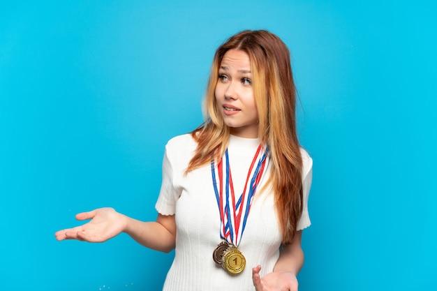 Ragazza adolescente con medaglie su sfondo isolato con espressione di sorpresa mentre guarda di lato
