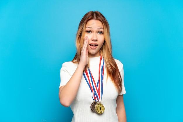 Ragazza adolescente con medaglie su sfondo isolato con espressione facciale sorpresa e scioccata