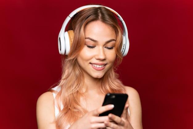 Ragazza dell'adolescente con i capelli rosa sopra la musica d'ascolto della parete rossa isolata e che osserva al cellulare