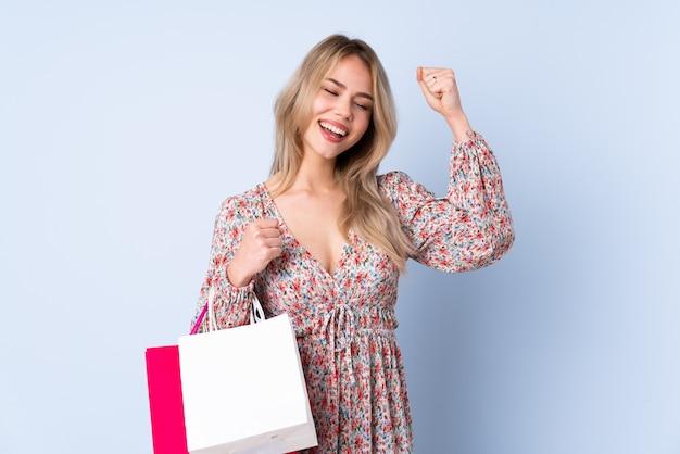 Ragazza dell'adolescente con il sacchetto della spesa isolato sulla parete blu che celebra una vittoria