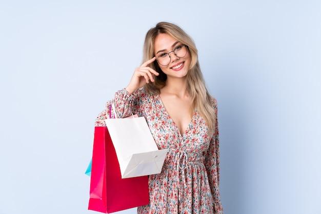 Ragazza dell'adolescente con il sacchetto della spesa isolato sull'azzurro con gli occhiali e felice
