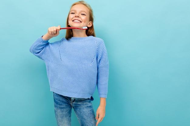 La ragazza adolescente con spazzolino da denti consiglia di lavarsi i denti