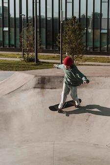 Adolescente divertirsi con lo skateboard all'aperto