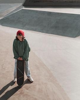Adolescente che si diverte a fare skateboard fuori allo skatepark