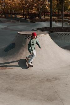 Adolescente divertirsi con lo skateboard al parco