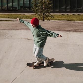 Adolescente divertirsi con lo skateboard allo skatepark