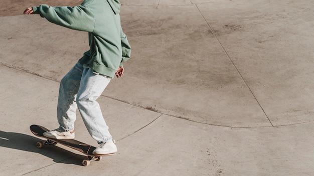 Adolescente divertirsi con lo skateboard con copia spazio