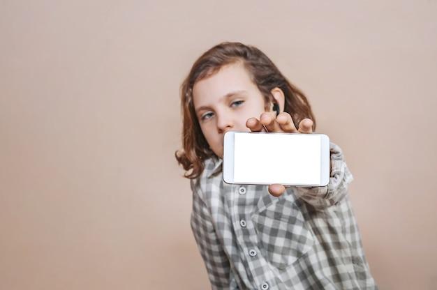 Un adolescente tiene uno smartphone in mano su uno sfondo chiaro. modello.